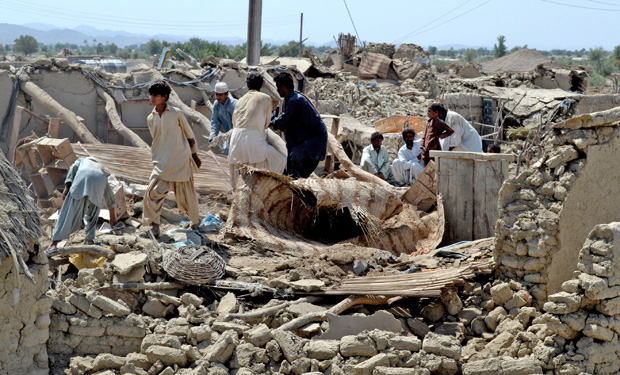 Pakistani villagers look for belongings amid the rubble of their dest